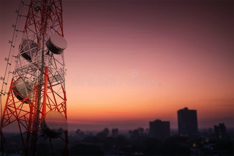 电信耸立和卫星盘与乡下区域剪影的电信网络在日出的 图库摄影