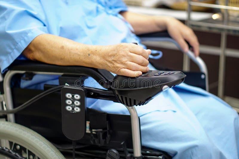 电动轮椅的亚裔资深或年长老妇人妇女患者有遥控的在护理的医院病房 库存照片