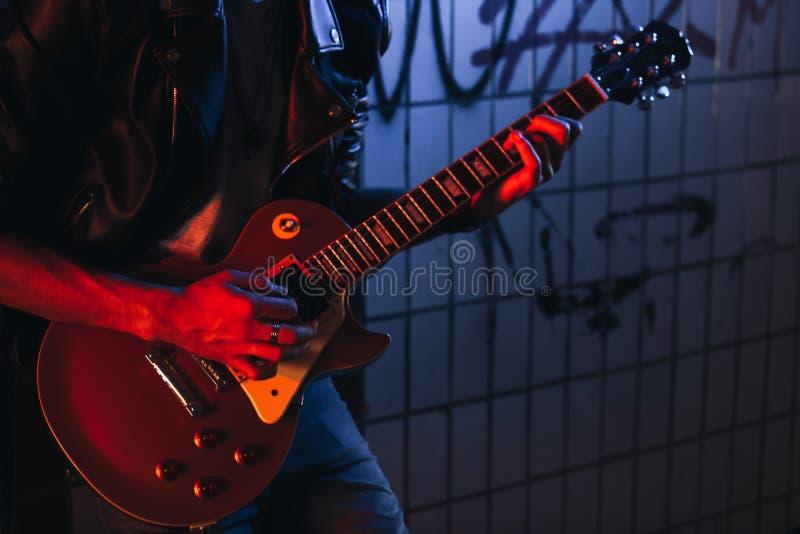 电吉他在音乐家的手上 无业游民的生活方式 谋生金钱的使用 失业的音乐家 未来岩石 库存图片