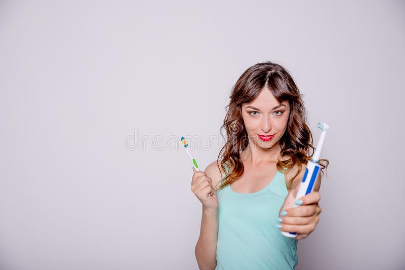 电和传统牙刷 口腔的卫生学 一年轻美女选择在电之间和 免版税库存照片