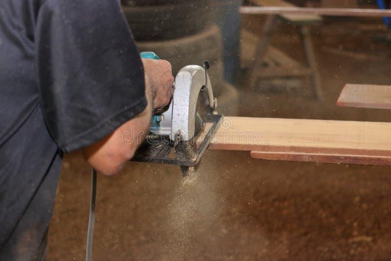 电圆锯由资深工作者锯一块木头在木匠业车间 免版税库存图片