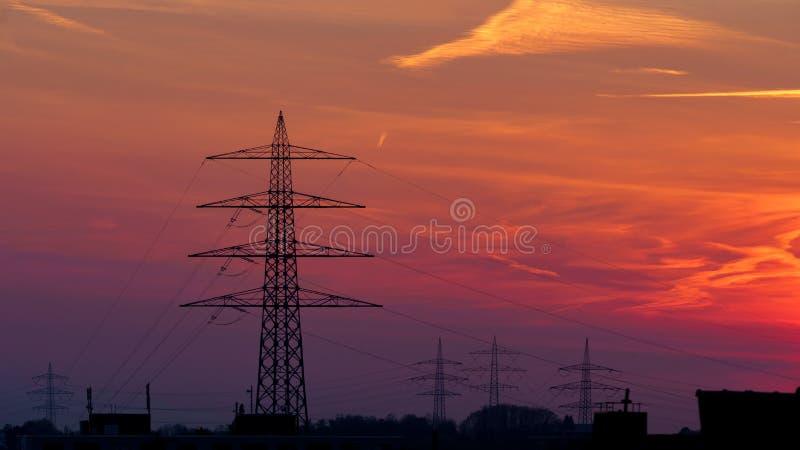 电在剧烈的橙色日落天空的定向塔剪影 库存照片