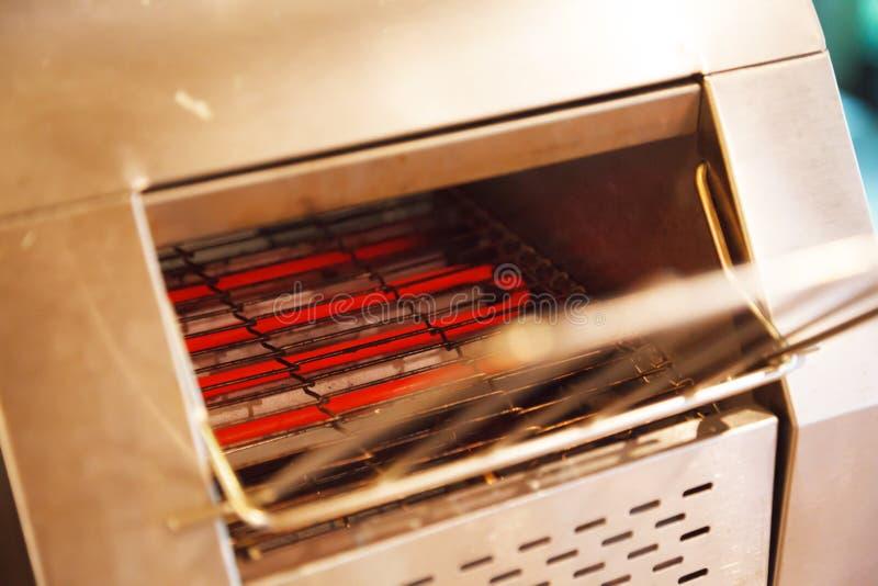 电子传动机多士炉烤箱敬酒通过申请热管理,从在烤箱房间的热的卷元素热源,于t 免版税库存照片