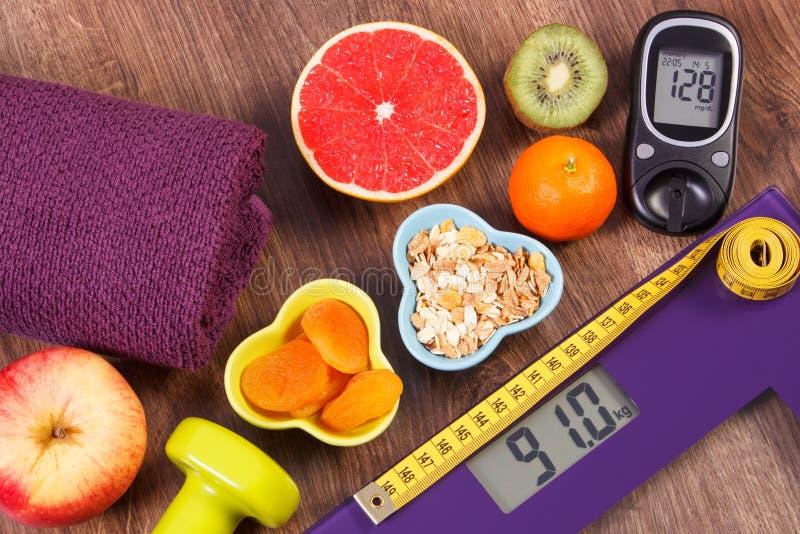 电子体重计和glucometer与测量、厘米、健康食物和哑铃,健康生活方式, d的结果 免版税库存照片