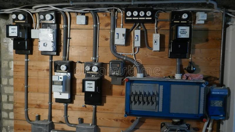 电子保险丝箱子和输电线在一个老公寓的地下室 库存照片