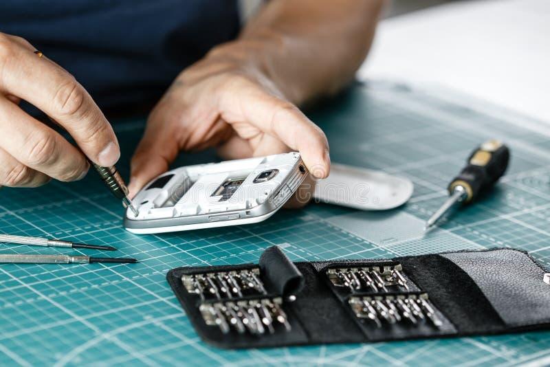 电子修理公司 检查的技术员拆卸的智能手机 免版税库存图片