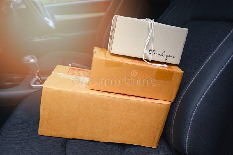 电子商务交付打包购物和在网上命令概念-在汽车座位的运输的购物的网上纸板箱 库存图片