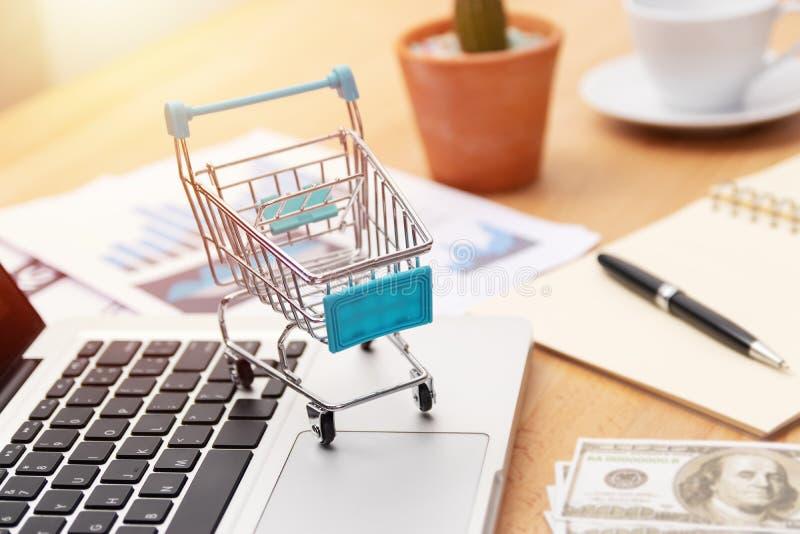 电子商务企业概念 在膝上型计算机键盘的手推车有营销图和金钱钞票的 在网上购物 库存图片