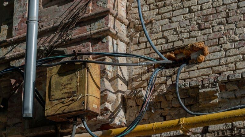 电子在砖红色墙壁上的金属老盘区 导线和气体黄色管子进入房子 侵害电和火 免版税库存照片