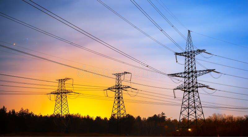 电子定向塔和高压输电线在晚上 免版税库存照片