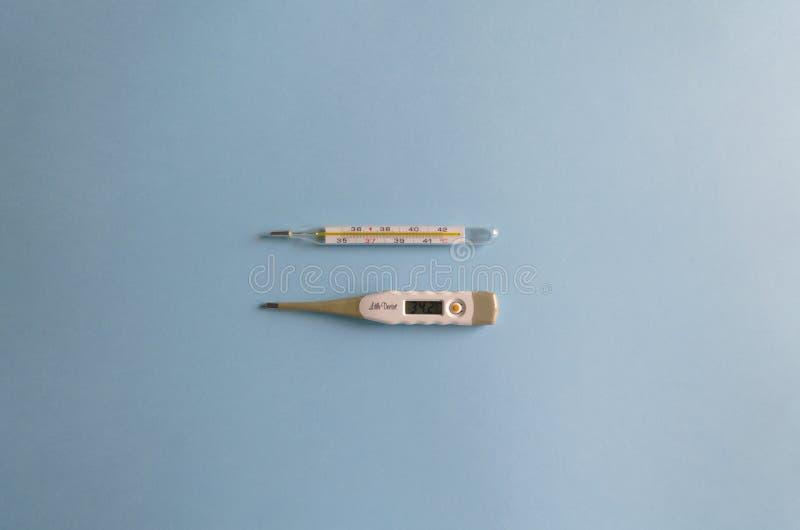 电子平的位置和测量在蓝色背景的温度的水银温度表 r 免版税库存照片