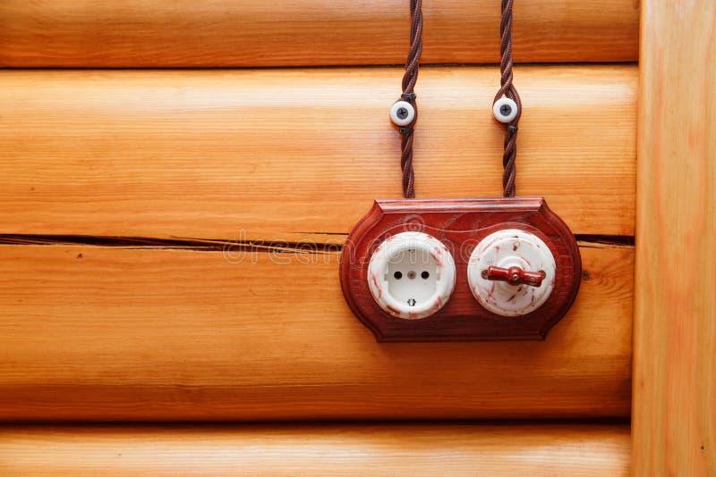 电子插口和开关在减速火箭的样式在木墙壁上 电工设计在房子里 免版税库存图片