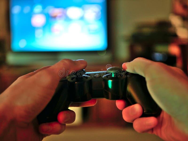 电子游戏赌博的操纵台管理员在游戏玩家手上举行了 免版税库存照片