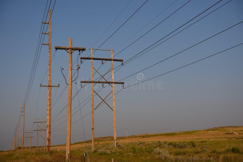 电子电线杆和顶上的高压输电线行在日落在农村怀俄明 图库摄影