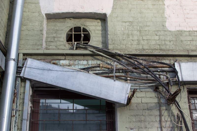 电子老被缠结的导线-,电话,天线,计算机,在一个被毁坏的房子的墙壁上的网络有分开的导线的在我 库存图片