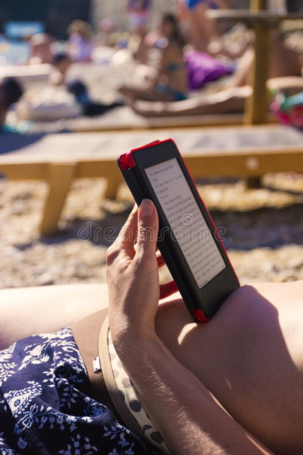 电子读者,读在海滩 免版税库存图片