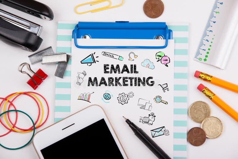 电子邮件营销概念 有文具和手机的办公桌 免版税库存照片