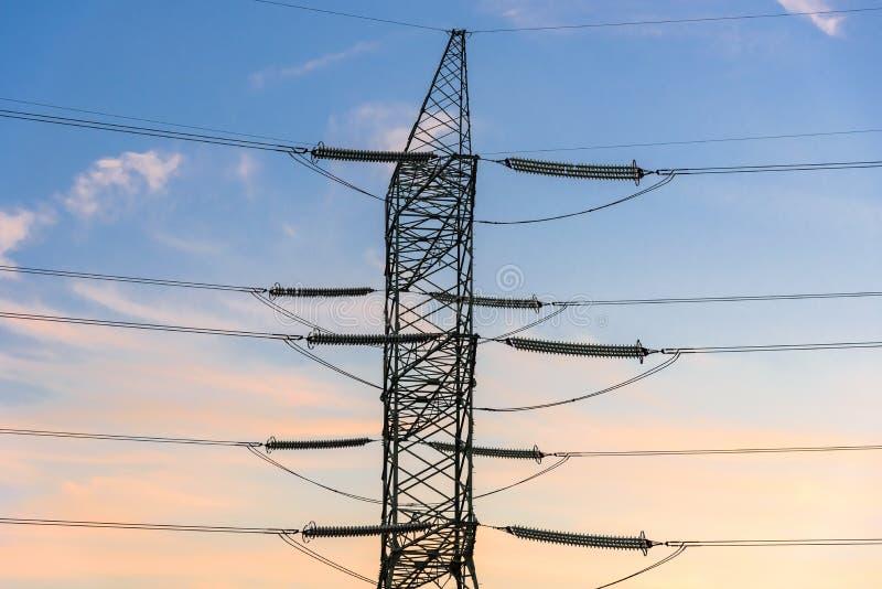 电定向塔和线特写镜头在日落 免版税库存照片