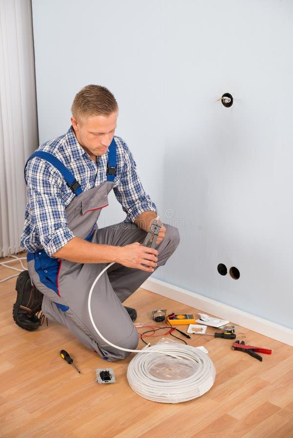 电工与与钳子的导线一起使用 免版税库存图片