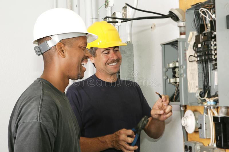 电工享受他们的工作 免版税库存图片