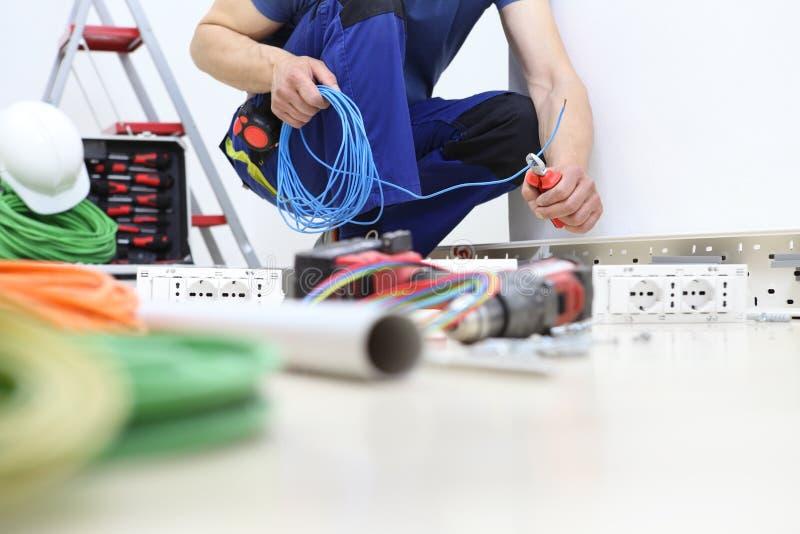 电工在与少年一起使用在手中切开了电缆,安装电子接线的电路 免版税库存图片
