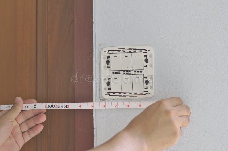 电工在墙壁上的屋子里测量电源开关盘区和门的距离 免版税库存照片