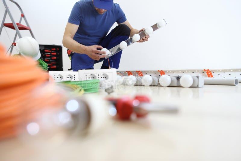 电工在安装灯,有电灯泡的工作,安装电路,电子接线 库存图片