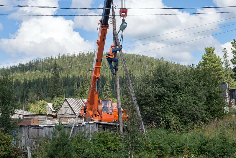 电工坐杆并且绑他与链子到进一步拆卸的起重机景气上 免版税库存照片