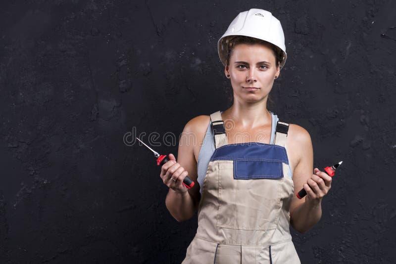 电工妇女画象一致和白色盔甲的拿着手中钢丝钳和少年 工作服的女工 库存照片