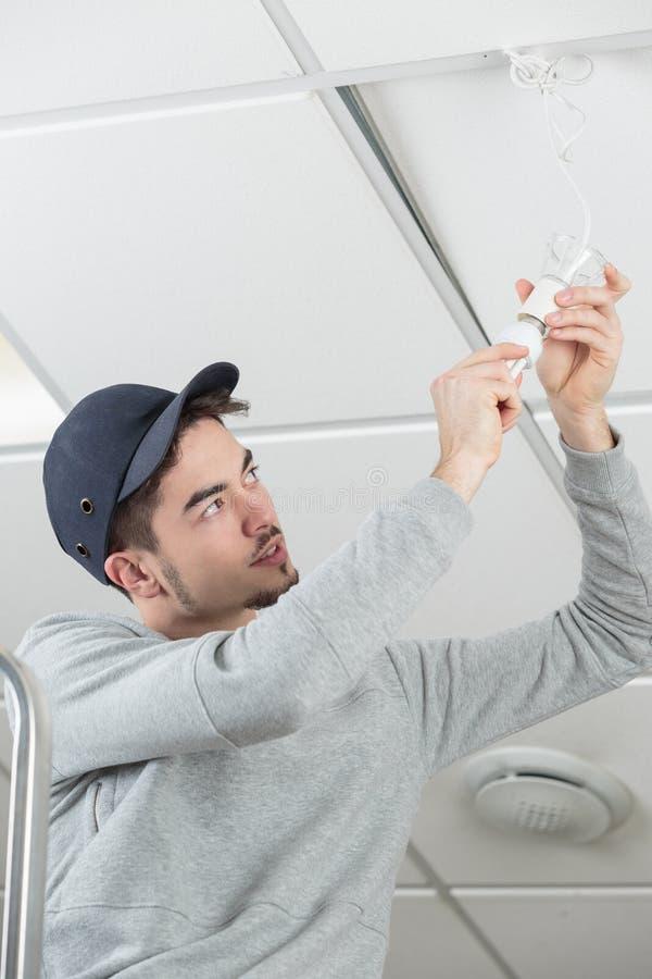 电工安装天花板日光灯的人工作者 免版税图库摄影