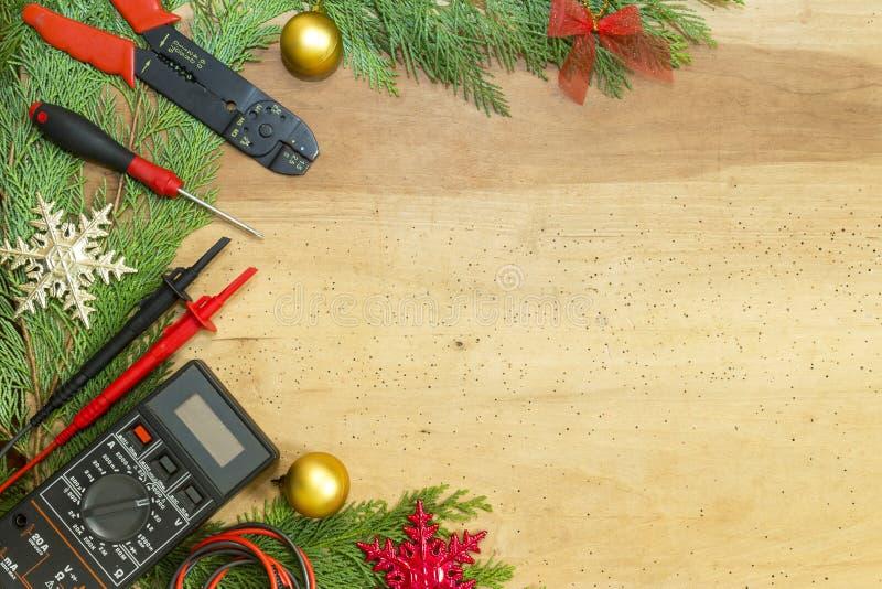 电工工具和仪器和圣诞节装饰在木背景 免版税库存图片