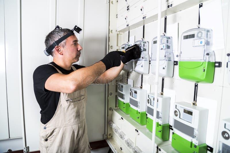 电工工程师与在保险丝开关盒的螺丝刀一起使用 图库摄影
