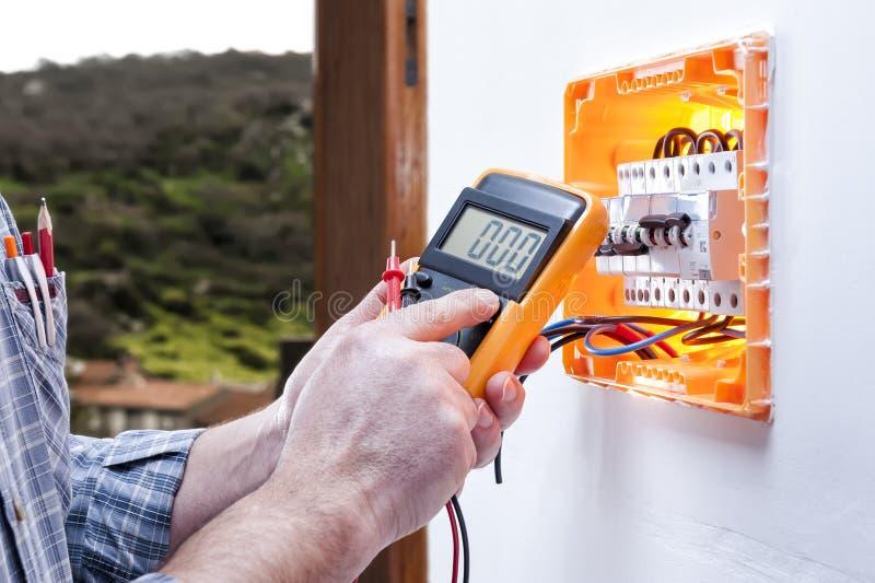 电工技术员修理住宅系统的电子盘区 免版税库存照片