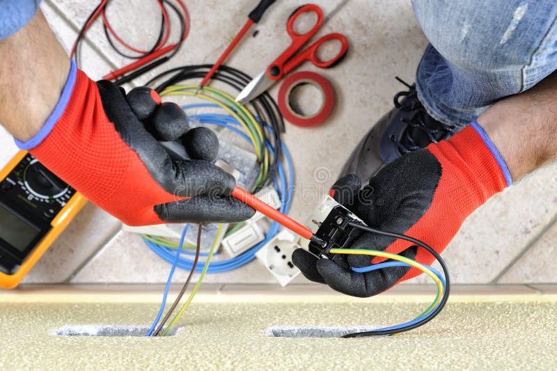 电工技术员在与在住宅电气系统的安全设备一起使用 免版税库存照片