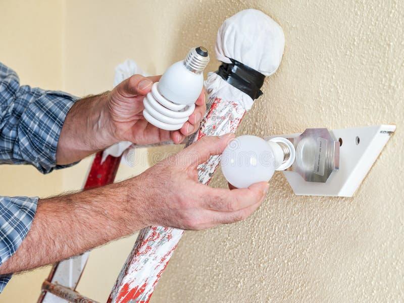 电工技术员在工作安装新的节能LED电灯泡 库存图片