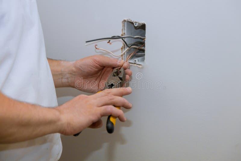 电工特写镜头的建筑递安装出口在有使用的专业工具墙壁 免版税库存照片