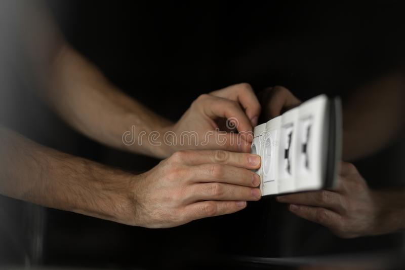 电工的手的特写镜头没有拆卸在黑玻璃墙上的任何工具和手套的一个白色电子出口 免版税库存图片