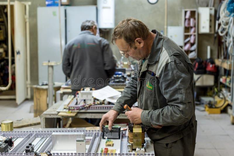 电工装配并且调整电子控制板 在装配a电路的工作  免版税库存照片