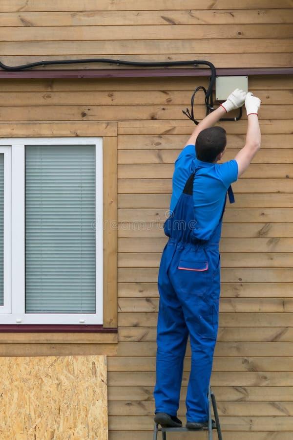 电工连接房子到电,背面图 图库摄影