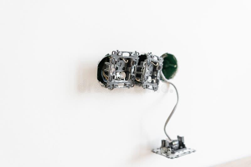 电工连接插口到在墙壁上的电线在绝尘室 螺丝刀,特写镜头电工手 免版税库存照片