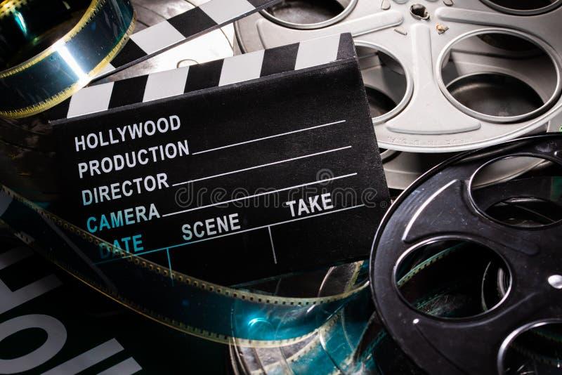 电影在木背景的拍板和影片轴 免版税库存图片