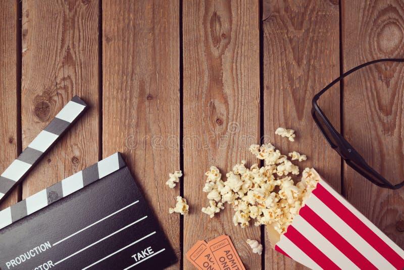 电影拍板、3d玻璃和玉米花在木背景 戏院概念 库存图片