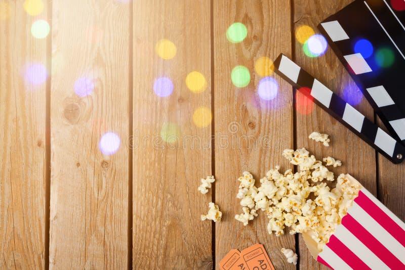 电影拍板和玉米花在木背景 戏院概念 库存图片