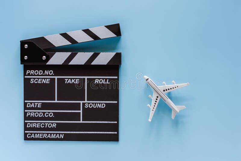 电影拍板和白色飞机模型在蓝色背景 库存图片