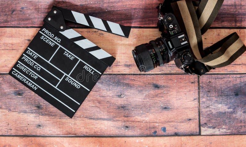 电影拍板和老照相机在木背景,电影射击 库存图片