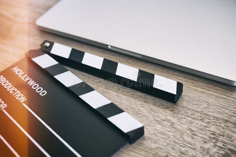 电影拍板和膝上型计算机在木头 免版税库存图片