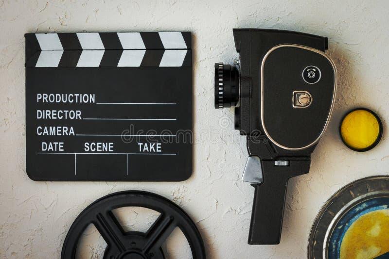 电影摄影机、clapperboard、影片箱子和黄色过滤器 图库摄影