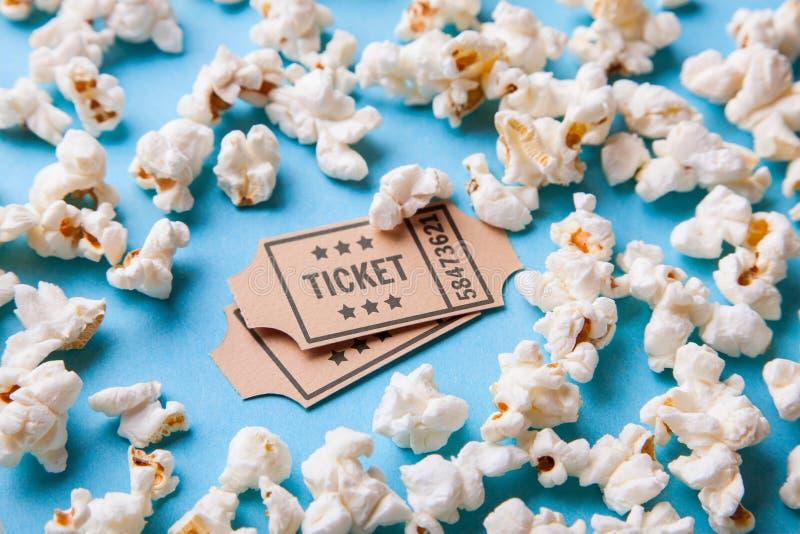 电影票和玉米花在蓝色背景 库存图片