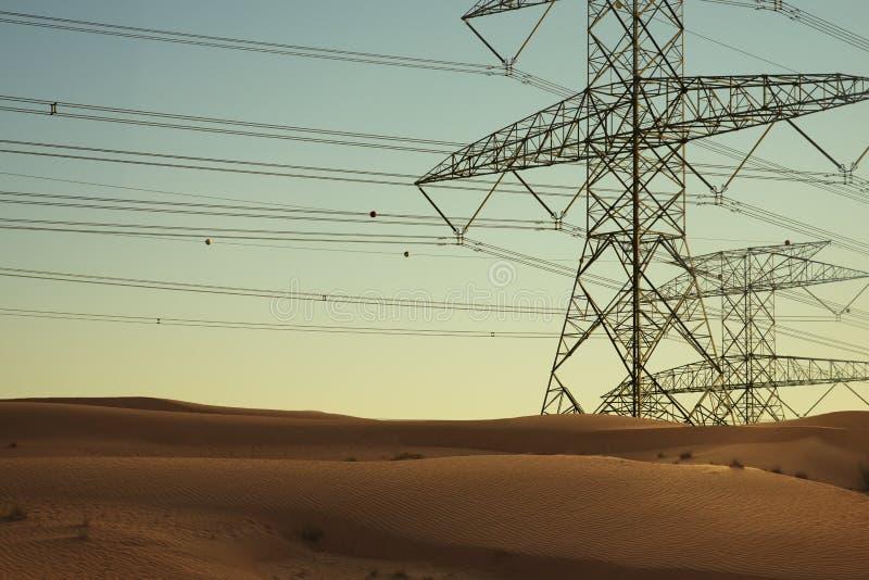电或高压在点心的输电线在日落 免版税库存照片
