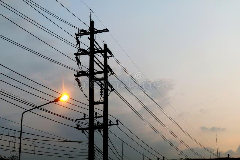 电杆力量缠结导线危险,在天空背景晚上架线电能并且点燃在街道路 免版税库存照片